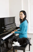 Mature woman at piano with her cat — Stock Photo