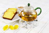 Fresh Green Tea in Glass Pot with Lemon Cake on the side — Stock Photo