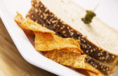 Golden Chips in front of Sandwich on White Plate — Stockfoto