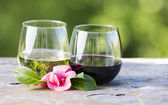 Red and White Wine with Pink Flower outdoors — Stock Photo