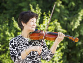 Senior Asian Woman Playing Violin outdoors — Стоковое фото