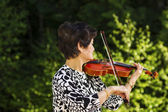 Senior woman playing music outdoors — Stockfoto