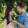 Young Adult Couple Sharing Drinks Outdoors — Stock Photo