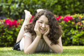 Young girl with big smile while lying down on lawn outside — Stok fotoğraf