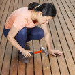 Mature woman adjusting boards on wooden cedar deck — Stock Photo