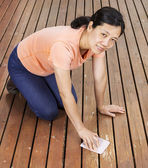 Matue woman sanding natural cedar wooden deck by hand — Stock Photo