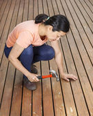 Mature woman adjusting boards on wooden cedar deck — Stock Photo