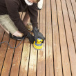 Stock Photo: Mature mperforming maintenance on home wooden deck