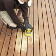Mature man performing maintenance on home wooden deck — Stock Photo
