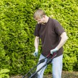 Mature man starting lawnmower — Stock Photo #26218895