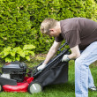 Mature man installing grass bag on old lawnmower — Stock Photo #26218907