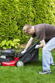 Mature man installing grass bag on old lawnmower — Stock Photo
