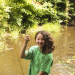 Very happy young girl catches small trout  — Stock Photo