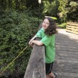 Stock Photo: Young Girl Smiles while Fishing off Bridge