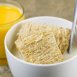 Whole grain cereal with honey and a glass of fresh orange juice — Stock Photo #28958437