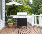 Large barbecue cooker on cedar deck — Stock Photo