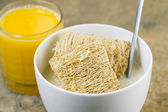 Whole grain cereal with honey and a glass of fresh orange juice — Stock Photo