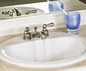 Casa de banho branco pia e torneira na posição aberta com água limpa — Foto Stock