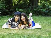 Young Adult Couple Lying on Blanket Outdoors — Stock Photo