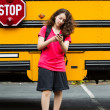 Girl walking away from School Bus while texting on her phone  — Stock Photo