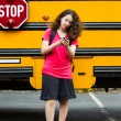 Stock Photo: girl walking away from school bus while texting on her phone