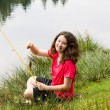 Young Girl Sitting Down and Catching Fish on the Lake  — Stock Photo