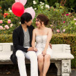 Young Adult Couple Sitting down on Bench in front of Rose Garden — Stock Photo