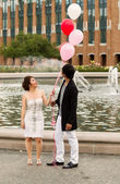 Young Adult Couple Watching Balloons as they hold them together — Stock Photo