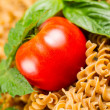 Single Ripe Tomato in pile of uncooked pasta and basil — Stock Photo #31823281