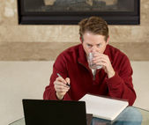 Mature man drinking water while working on assignments at home — Stock Photo