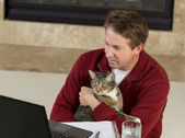 Mature man holding his family pet while working at home — Foto Stock