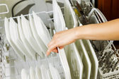 Loading dinner plates into the lower dish rack of dishwasher — Stock Photo