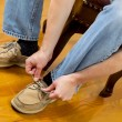 Foto de Stock  : Mputting on Shoes while sitting on footstool