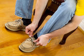 Man putting on Shoes while sitting on footstool — Stock Photo