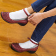 ストック写真: Womputting on causal shoes while sitting on footstool at home