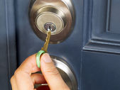 Female hand putting house key into door lock — Stock Photo