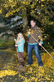Dad and daughter cannot keep up with the falling leaves — Stock Photo