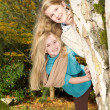 Sisters playing in the park during a nice autumn day — Stock Photo