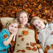 Mom and her daughters lying on a bed of leaves during the fall s — Stok fotoğraf