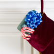 Christmas stocking with Real Candy Canes and present hanging on — Stock Photo