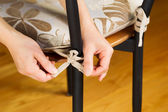 Putting seat cushion on chair — Stockfoto