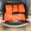 Stock Photo: Placing Salmon into Oven for Baking