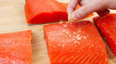 Putting Sea Salt on Red Salmon — Foto Stock