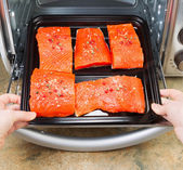 Placing Salmon into Oven for Baking — Stock Photo