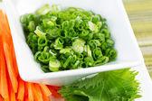 Čerstvé zelené cibule a plátky mrkve — Stock fotografie