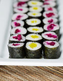 Long Plate filled with Pickled Hand Rolled Sushi — Stock Photo