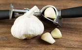 Fresh Garlic with Press on Wooden Board  — Stock Photo