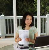 Mature woman working at home office with tax forms  — Stock Photo
