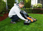 Mature man putting battery into electric Lawn Mower  — Stock Photo