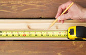 Hand measuring wooden board — Stock Photo